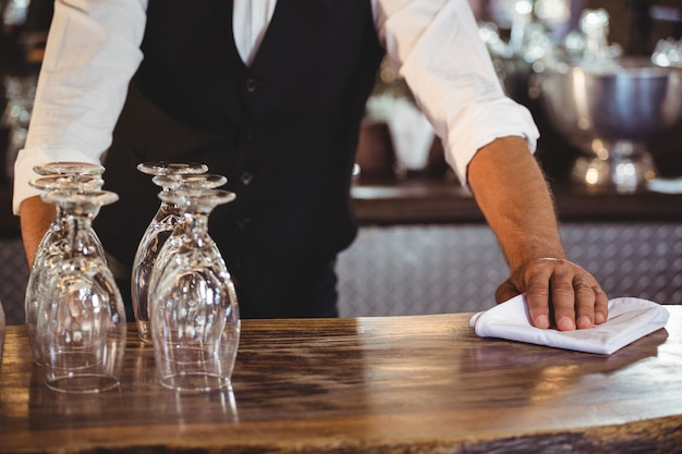 Mid section of bartender cleaning a bar counter