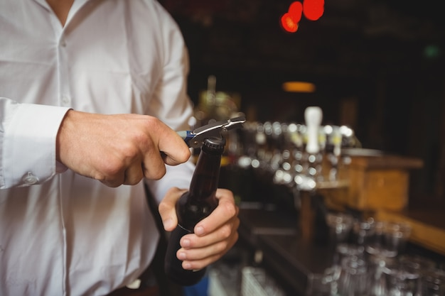Mid section of bartender opening a beer bottle