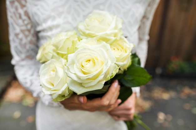 Mid section of bride holding bouquet of roses in hands