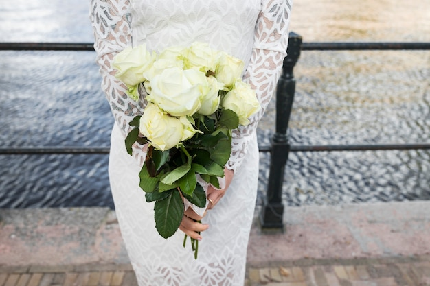 Mid section of bride holding bunch of roses in hands