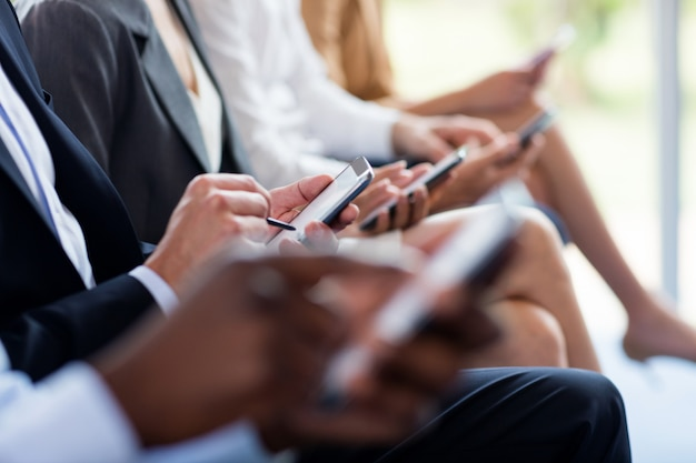 Mid section of business executives using mobile phone