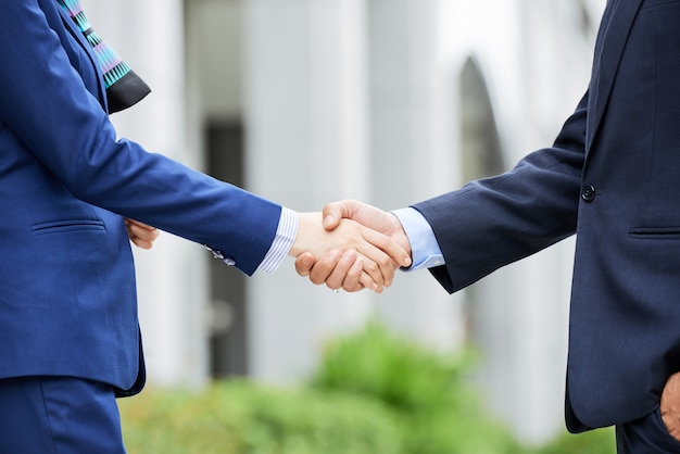 Mid-section of business people shaking hands outdoors