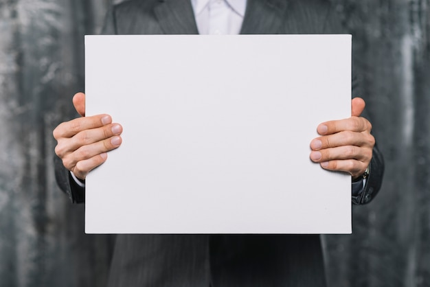 Mid section of a businessman showing blank white placard