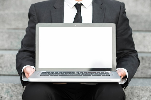 Mid section of a businessman showing an open laptop with blank white screen