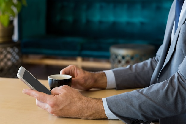 Mid-section of businessman using mobile phone while having a cup of tea