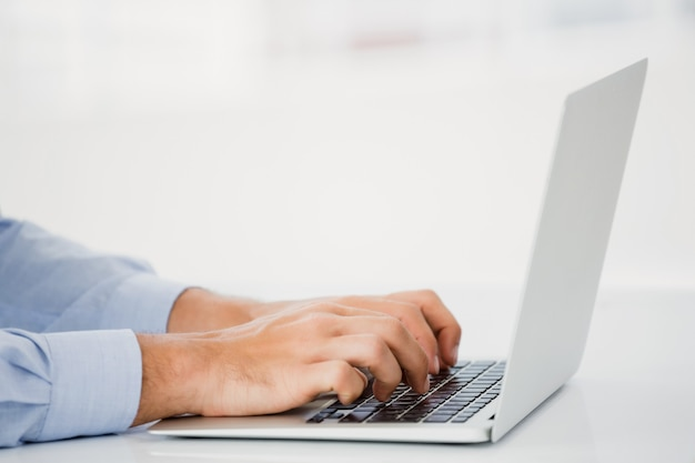 Mid-section of businessman working on laptop