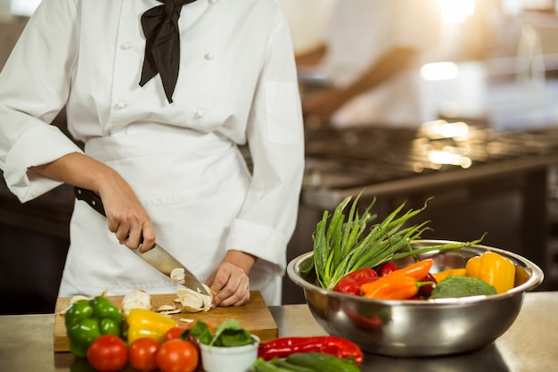 Mid section of chef cutting vegetables
