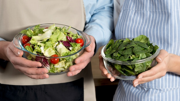 Mid-section of couple holding bowl of healthy salad and basil leafs