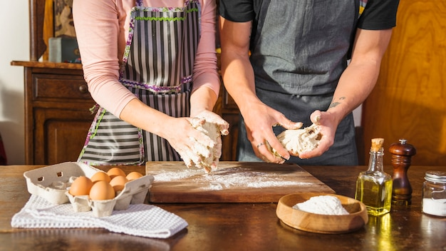 Mid section of couple preparing dough with baking ingredients on wooden table