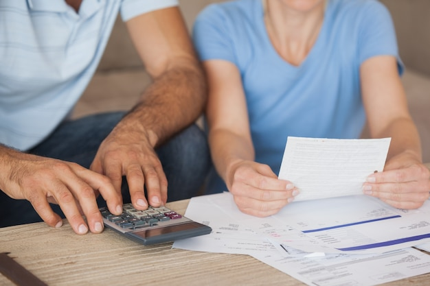 Mid section of a couple with bills and calculator