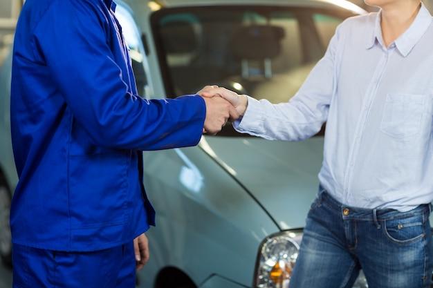 Mid-sezione di stringere la mano a clienti meccanico