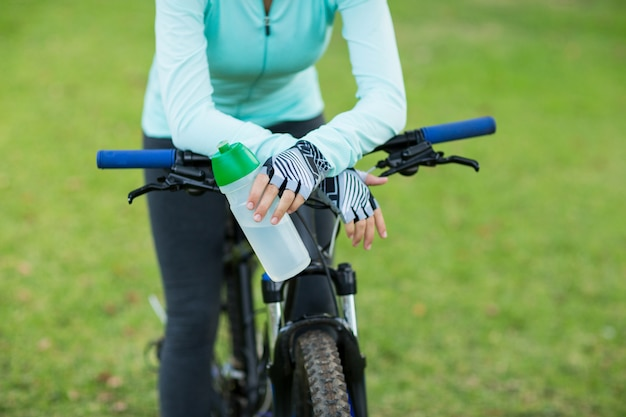 Mid section of cyclist holding water bottle