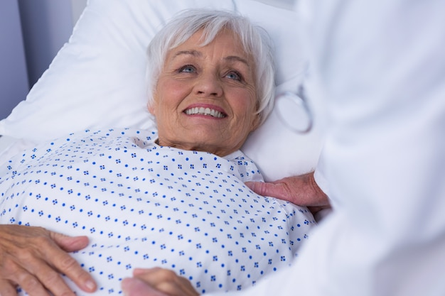 Mid-section of doctor consoling senior patient