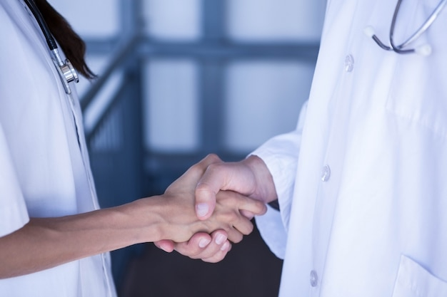 Mid section of doctors shaking hands in hospital