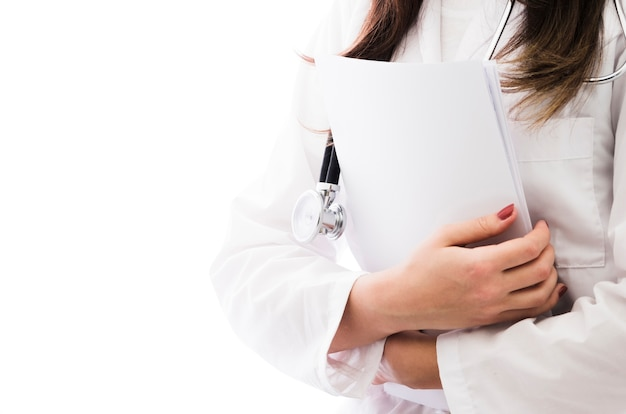 Mid section of a female doctor with stethoscope around her neck holding medical report in hand