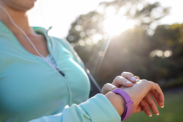 Mid section of female jogger checking her fitness band