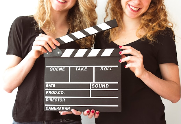 Mid section of female sister holding clapperboard