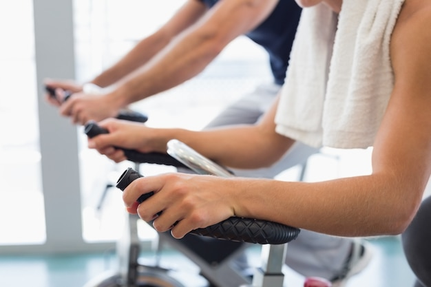 Mid section of fit couple working on exercise bikes at gym