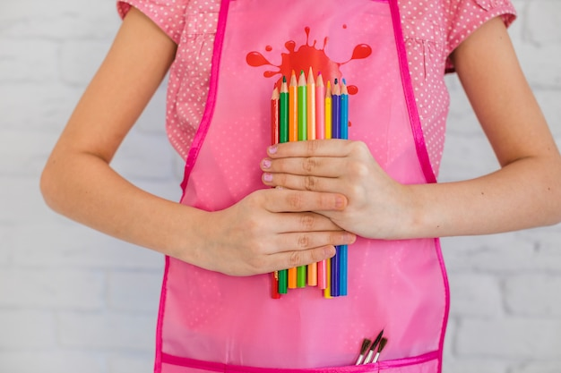 Mid section of a girl holding many multicolored colored pencils in hands