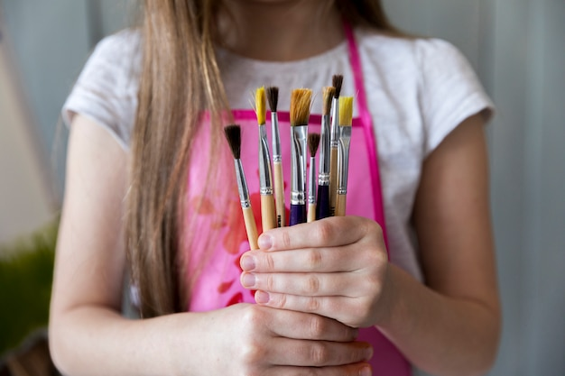 Mid section of a girl holding many paintbrushes in hand