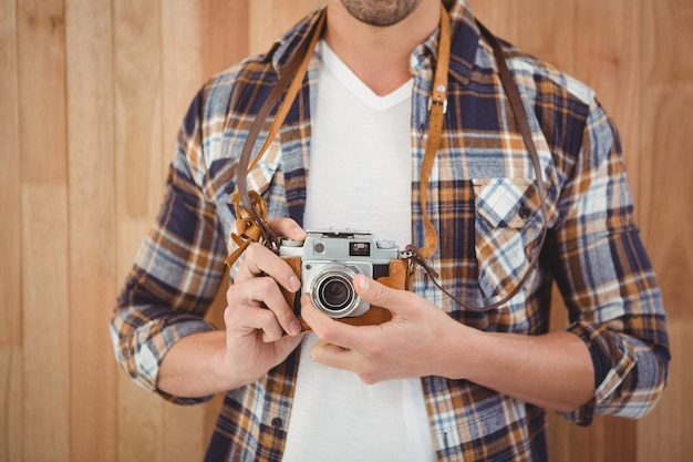 Mid section of hipster using camera against wooden wall