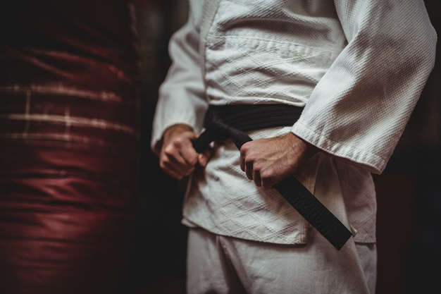 Mid section of karate player tying his belt
