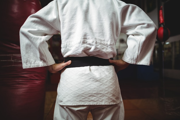 Mid section of karate player with hands on hips