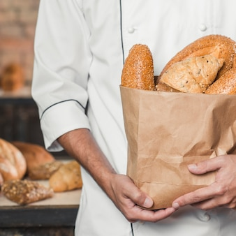 Mid section of maker holding baked breads in paper bag