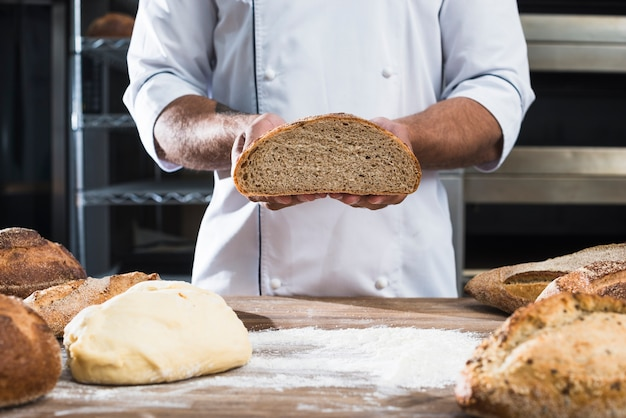 Mid section of a male baker holding bread