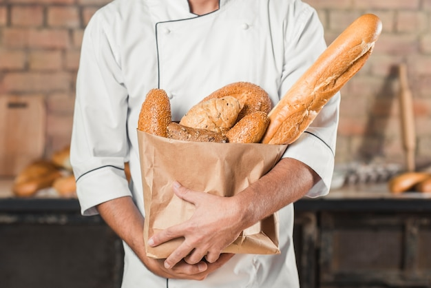 Mid section of male baker holding different type of breads in paper bag