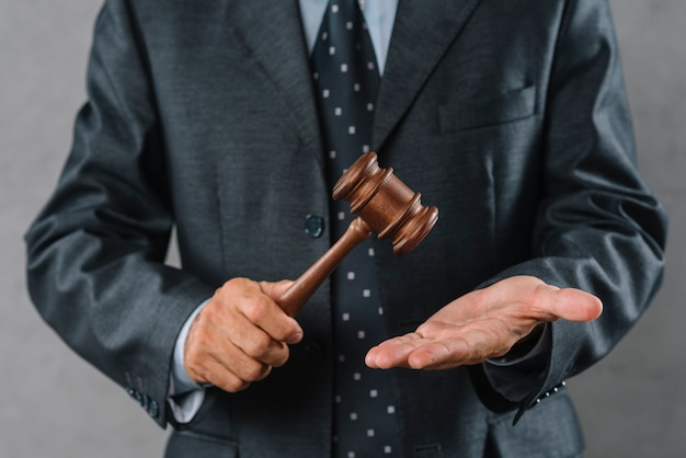 Mid section of male lawyer holding wooden mallet in hand