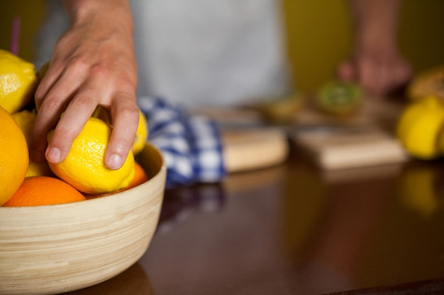 Mid-section of male staff picking a lemon fruit from a bowl