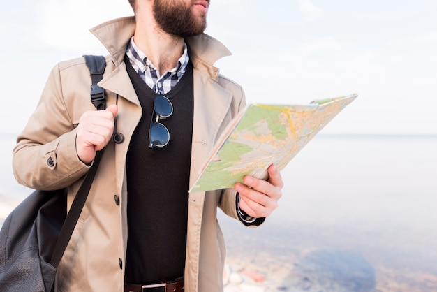 Mid section of a male traveler holding map and handbag