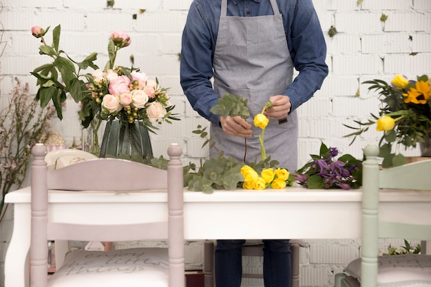 Mid section of man arranging the flowers over the table