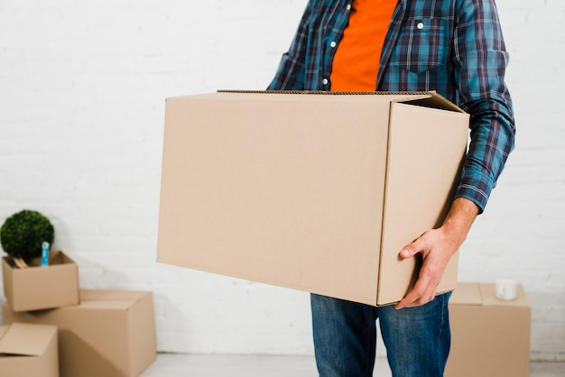Mid section on a man carrying cardboard box in hand