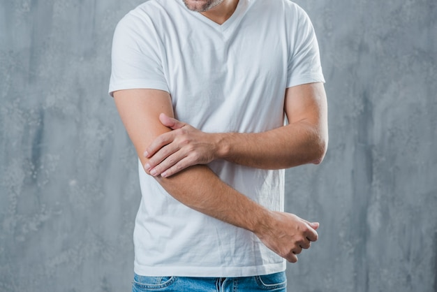 Mid section of a man having elbow pain standing against grey background