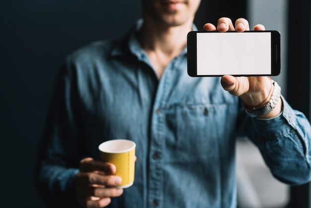 Mid section of a man holding disposable coffee cup showing mobilephone screen