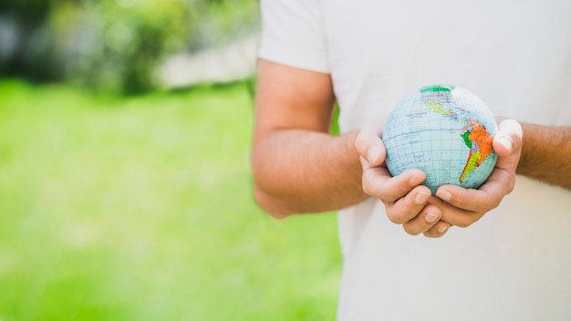 Mid section of man holding globe in hand