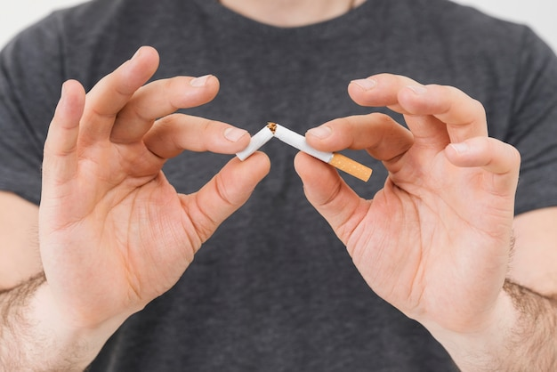 Mid section of a man's hand breaking the cigarette