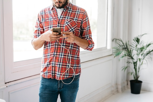 Mid section of a man standing near the window using smart phone