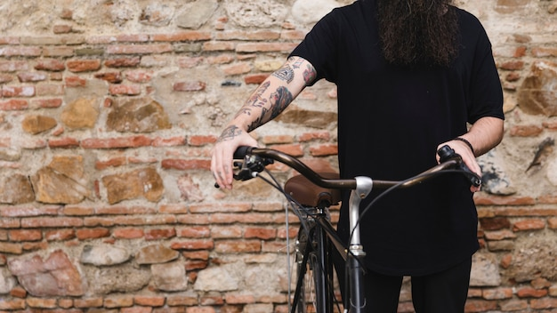 Mid section of a man standing with bicycle against wall