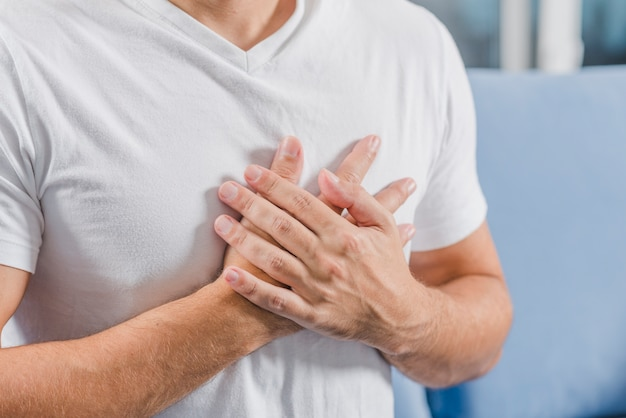 Mid section of a man touching his chest with hands