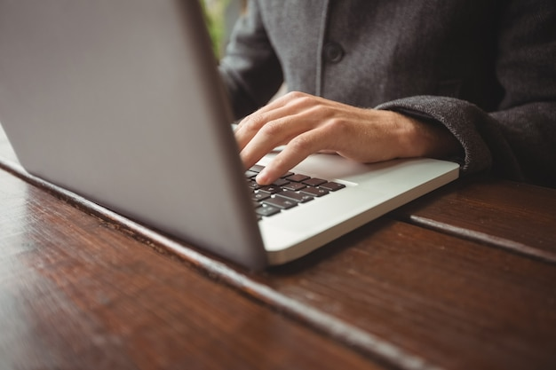 Mid section of man using laptop