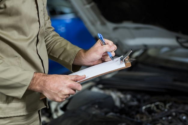 Mid-section of mechanic preparing a check list