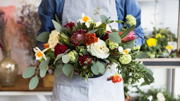 아름다운 꽃 화병을 들고 남자 플로리스트의 중간 부분