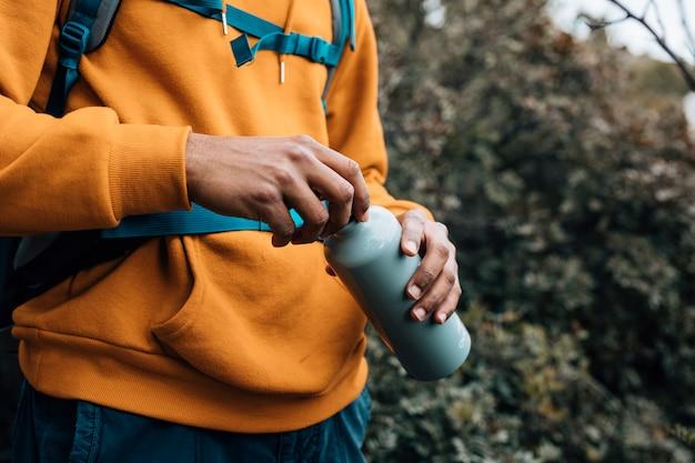 Средняя часть мужчины, открывающего крышку бутылки с водой