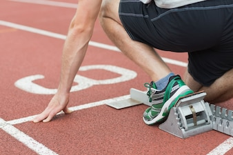 Mid section of a man ready to race on running track