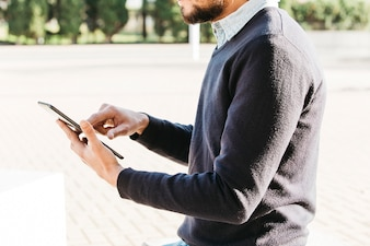 Mid section of a man sitting in the park using touch screen mobile phone