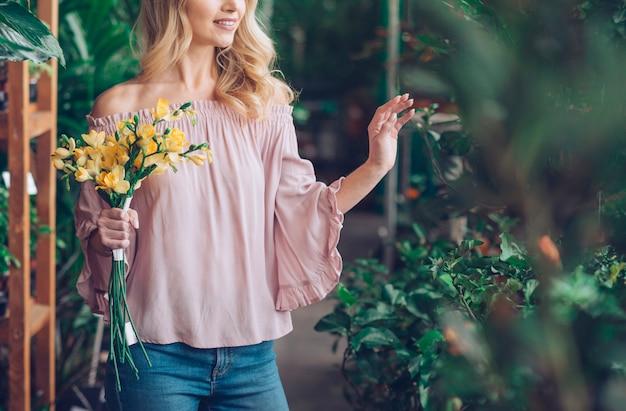 植物保育園で黄色い花の花束を保持している若い女性の半ばセクション