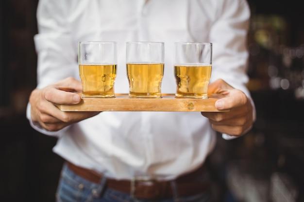 バーカウンターでウイスキーショットグラスのトレイを保持しているバーテンダーの中央部